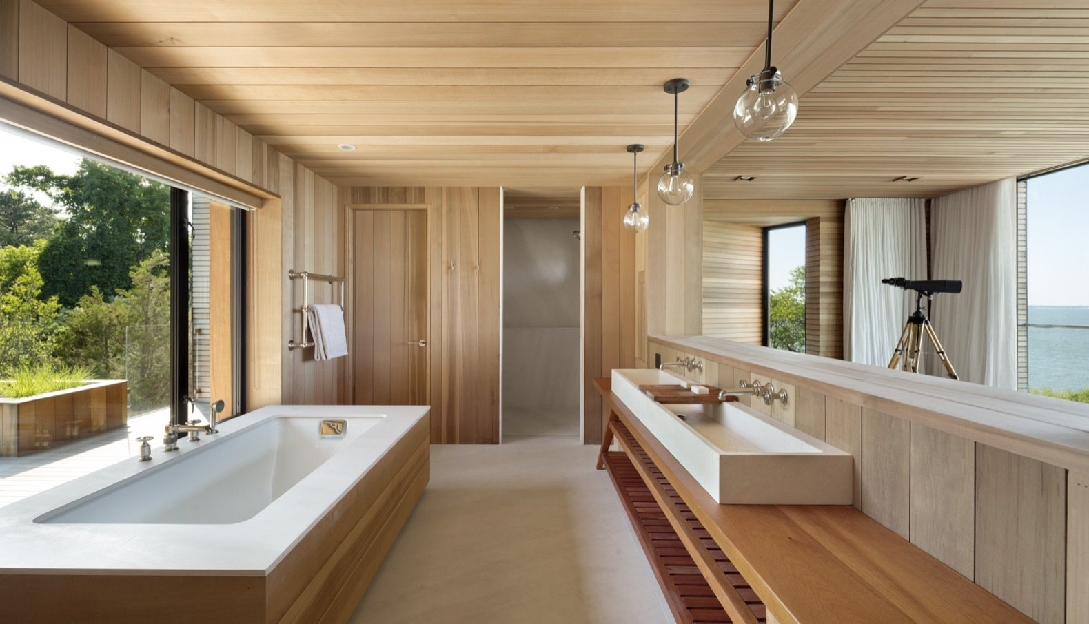 Bath, Soaking, Vessel, Enclosed, Pendant, and Wood The bathroom fixtures include Waterworks, Duravit, Kohler, and Geberit.  Best Bath Soaking Pendant Wood Photos from This Hamptons Getaway Blends Seamlessly Into a Lush Landscape
