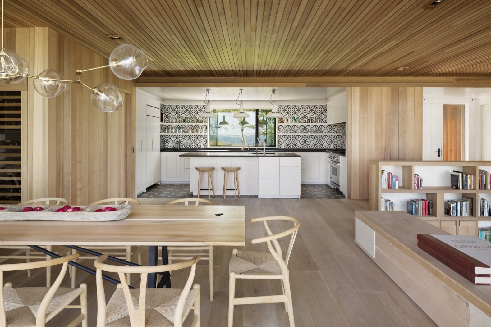 Dining, Accent, Medium Hardwood, Pendant, Table, and Chair Enveloped in cedar and reclaimed white oak, the interiors exude a sense of warmth.   Best Dining Accent Medium Hardwood Table Pendant Photos from This Hamptons Getaway Blends Seamlessly Into a Lush Landscape