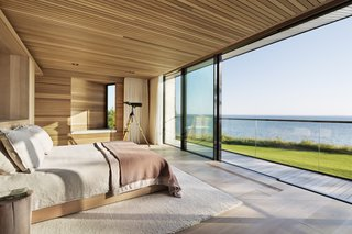 Bathed in light, the master bedroom overlooks stunning waterfront views.