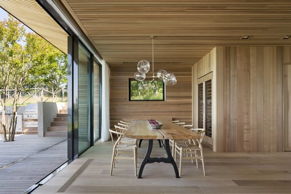 Sliding doors provide a seamless connection between the dining room and the outdoor dining and kitchen areas.