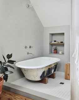 The clawfoot tub was a salvaged find, while reclaimed wood was used for the shelving.