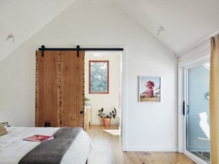 A sliding barn door built of salvaged pine separates the master bedroom from the bath.