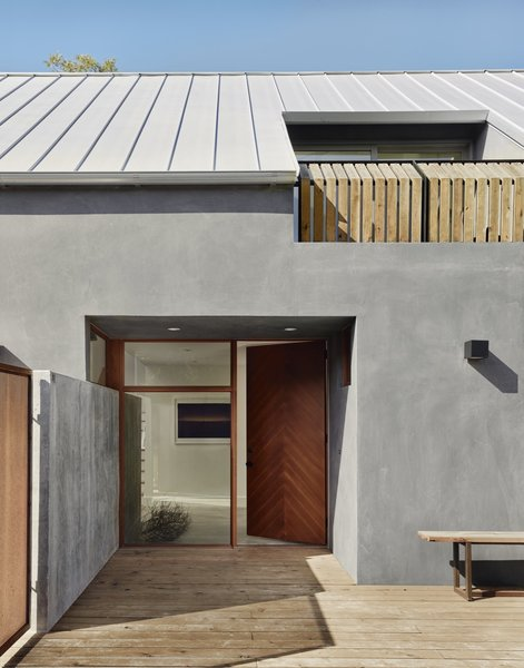 The entrance is located to the side of the house. The recessed Douglas fir front door was built by Austin's Honea Woodworks. The roof is Galvalume standing-seam metal.