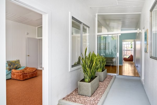Formerly an enclosed patio, the entrance foyer was remodeled by previous owners into a hallway and room, which is now separated by a new wall.
