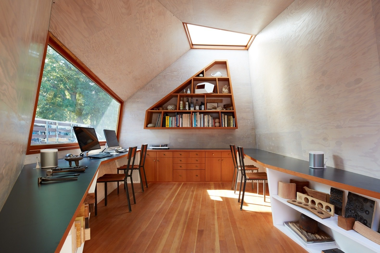 "Office, Storage, Desk, Bookcase, Medium Hardwood Floor, Shelves, and Chair The custom-made skylight ""marries traditional boatbuilding materials with details borrowed from a car sunroof."" The worktops are Formica 2297 Terril.  Photo 6 of 12 in An Experimental Micro-Office Glows Like a Lighthouse in L.A."