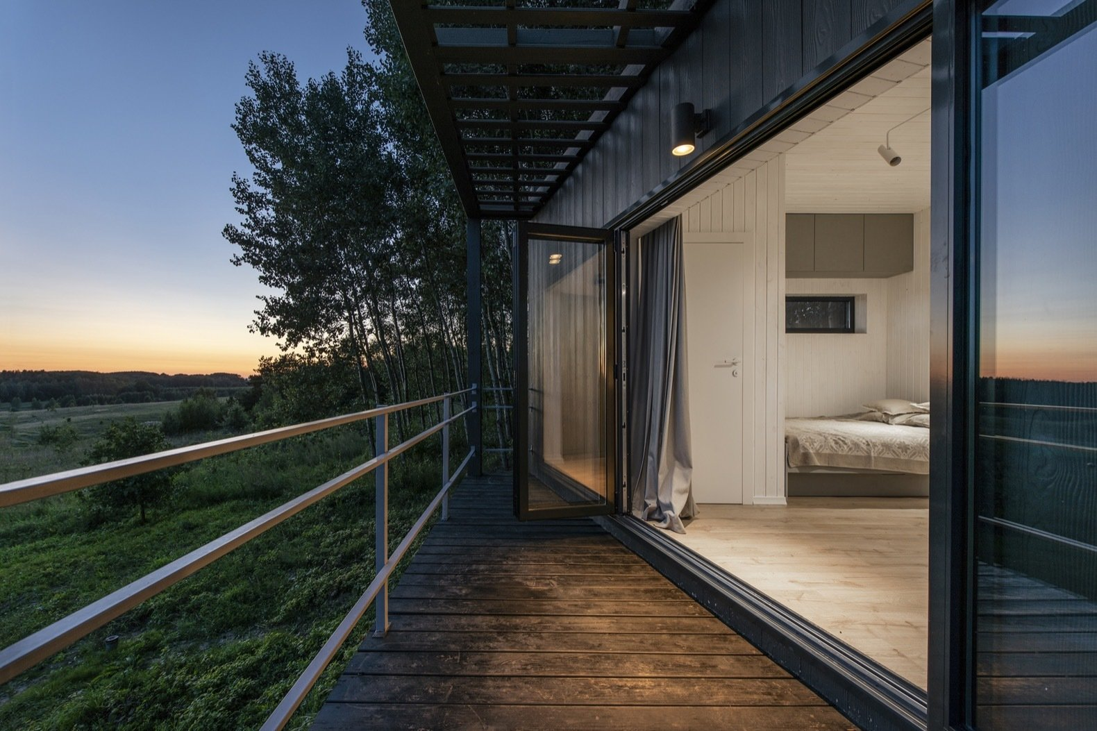 Outdoor, Wood Patio, Porch, Deck, Trees, Front Yard, Shrubs, Slope, Grass, and Small Patio, Porch, Deck The home is also equipped with an infrared heater and a wireless bluetooth speaker.   Photo 9 of 11 in Mingle With Mother Nature in This Tiny Prefab Getaway