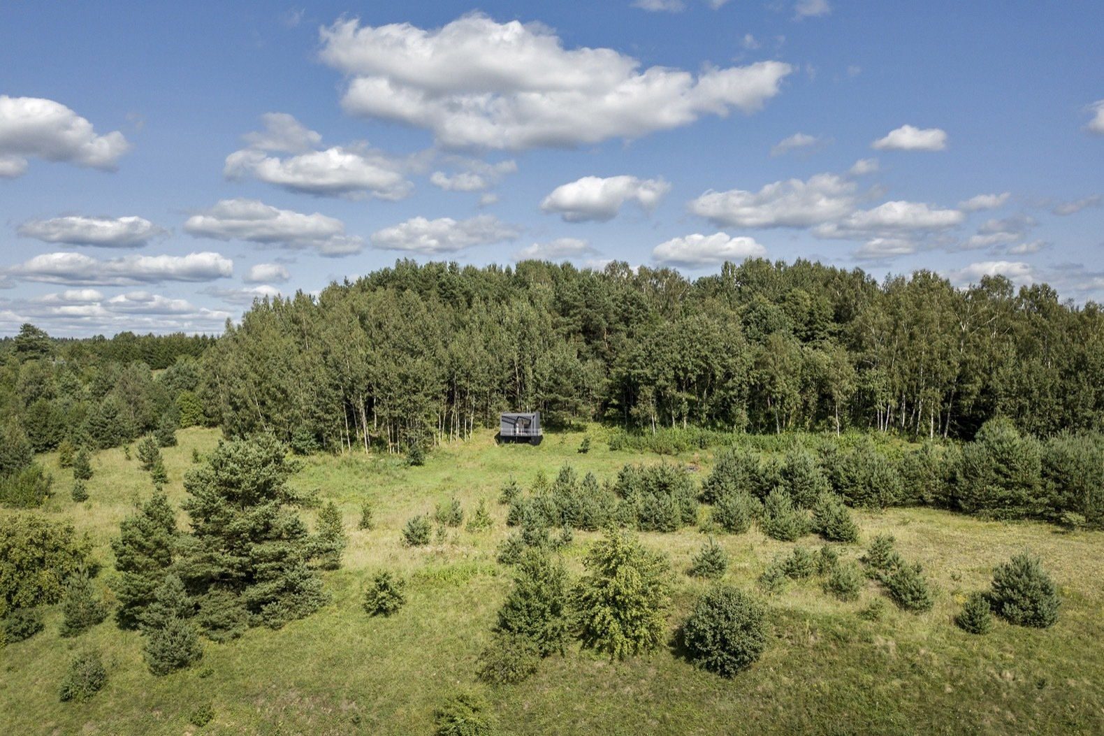 Outdoor, Shrubs, Grass, Woodland, Trees, and Slope Set on a wild 50-acre property, the Etno Hut is located within easy access from two major Lithuanian cities, Vilnius and Kaunas.  Photo 1 of 11 in Mingle With Mother Nature in This Tiny Prefab Getaway