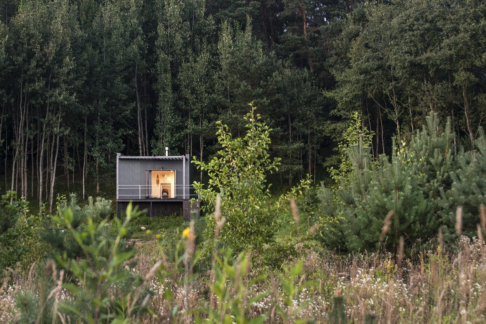 Exterior, Concrete Siding Material, Cabin Building Type, and Flat RoofLine Set on a slope, the property faces the forest to the north and sweeping views of the landscape to the south.   Photo 2 of 11 in Mingle With Mother Nature in This Tiny Prefab Getaway