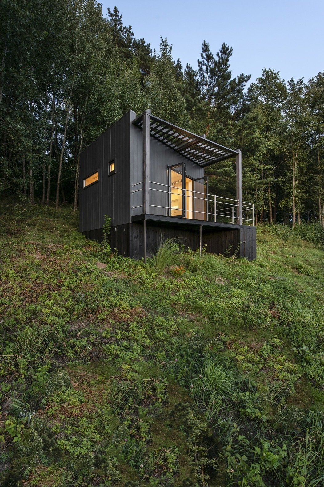 Exterior, Cabin Building Type, Concrete Siding Material, and Flat RoofLine The Etno Hut is elevated on a steel foundation screwed into the ground by hand. The space beneath the main volume was covered to hide cables, piping, and storage.    Photo 3 of 11 in Mingle With Mother Nature in This Tiny Prefab Getaway