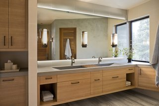 The lavish master bath features concrete counters with integrated sinks designed by the architect and design team.