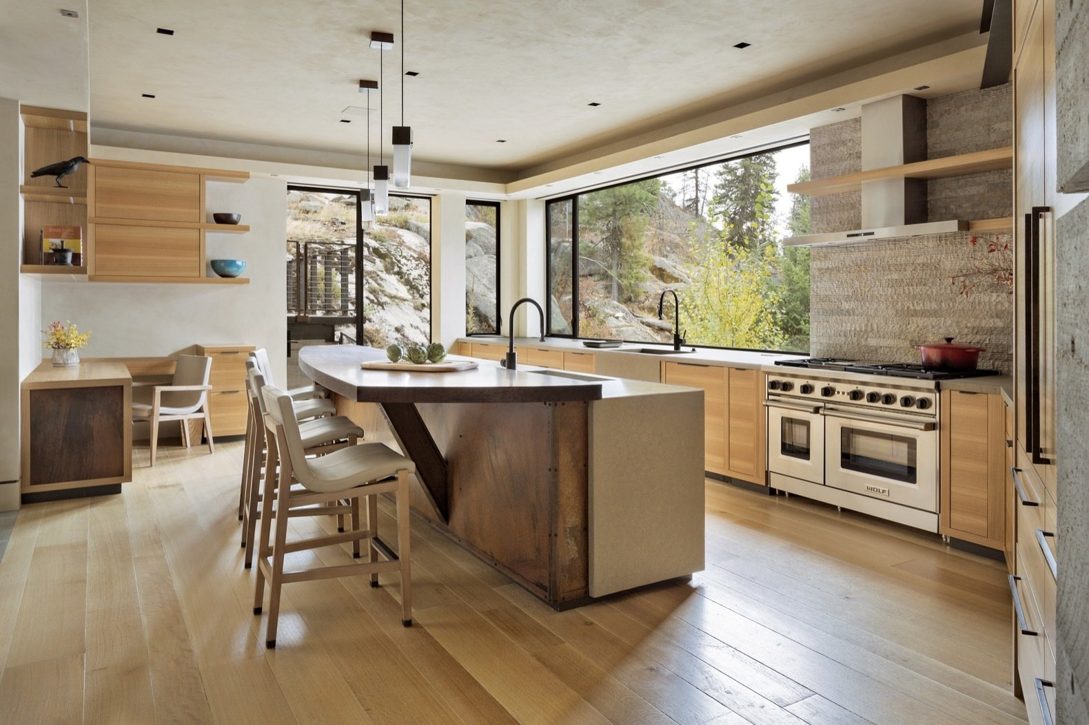 Kitchen, Dishwasher, Wall Oven, Range Hood, Cooktops, Medium Hardwood, Range, Recessed, Pendant, Wood, Refrigerator, and Concrete The light-filled kitchen is fitted out with glass fiber-reinforced concrete counters, quartern-sawn eucalyptus cabinets, as well as Sub-Zero, Wolf and Miele appliances.    Best Kitchen Cooktops Recessed Wall Oven Wood Dishwasher Photos from This Modern Cliff House Seamlessly Knits Into a Rocky Idaho Lakefront