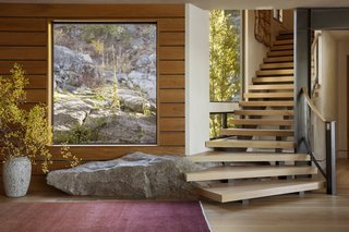 A boulder integrated into the entrance foyer and large, triple-glazed windows immediately set the scene for indoor/outdoor living. The curved stairs lead up to the bedrooms.