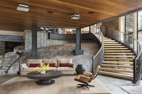 """A large piece of natural granite bedrock forms the backdrop to the game room, which is furnished with Round Iron Gear Table by Jerome Abel Segun and a Thayer Coggin 'Baxter' sofa. """"This large element in the game room features a small bar area which is also the transition zone from the sophisticated finishes of the majority of the house to a mine shaft theme, as one travels back into the mechanical area along rough-cut bedrock walls,"""" adds the firm."""