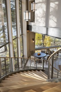 A view from the upper floor down the circular staircase to the game room below. The flaring, circular staircase was built using I-beams bent in Seattle.