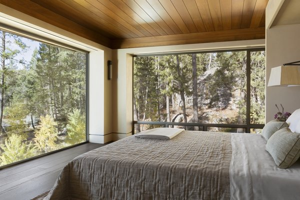 The master bedroom was crafted with a low wooden ceiling to create a sense of intimacy, balancing out the expansive walls of glass on two sides.