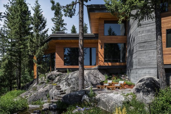 Walls of glass, horizontal roof planes, and a natural material palette enable this expansive home to feel like an extension of a dramatic boulder-strewn landscape in Idaho.