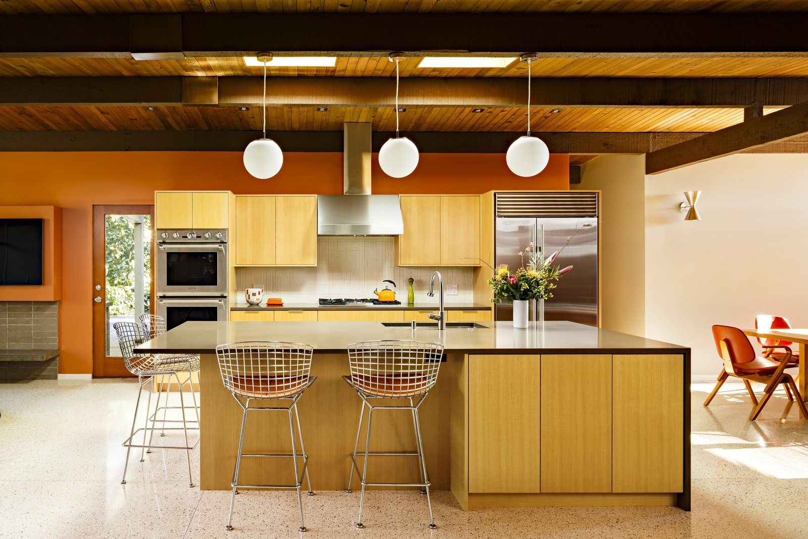 Kitchen, Wood Cabinet, Cooktops, Terrazzo Floor, Wall Oven, Engineered Quartz Counter, Range, Range Hood, Refrigerator, and Pendant Lighting The retrofit of this Portland midcentury-modern home takes inspiration from Richard Neutra, Saul Zaik, and John Yeon.    Best Photos from Acclaimed Architect Risa Boyer Reinvents Indoor/Outdoor Living