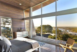 Ipe wood envelopes the master bedroom that overlooks spectacular views of the beach through a wall of glass.