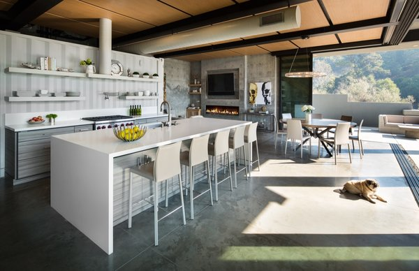 The ground floor features an open floor plan with combined living spaces and a centrally placed kitchen.
