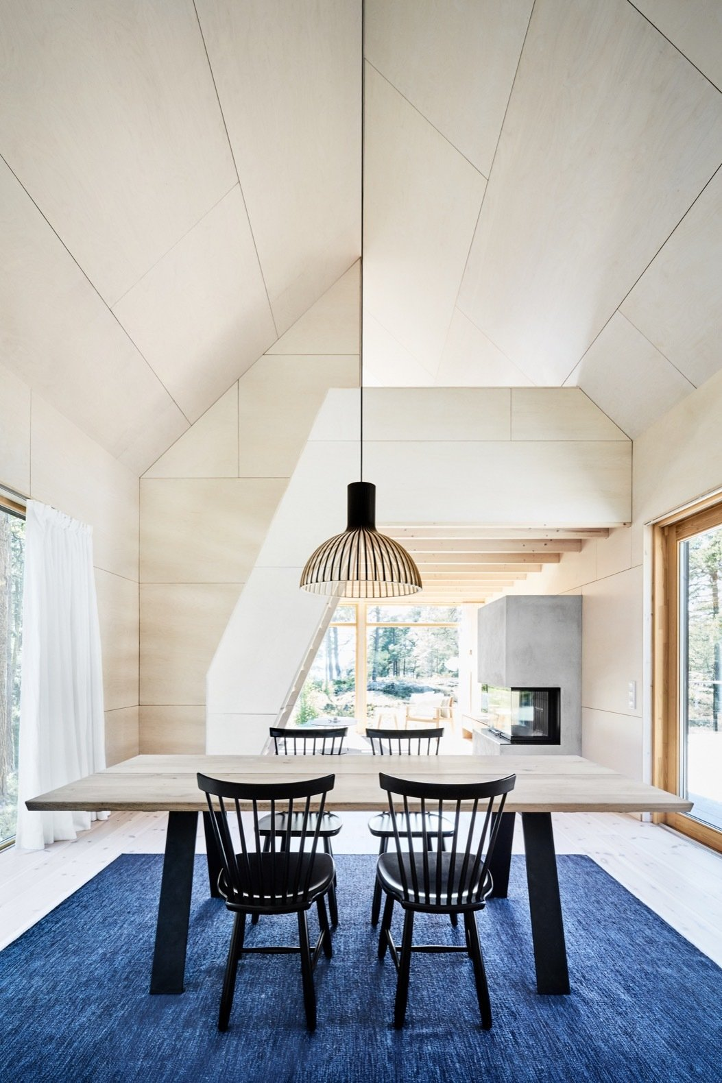 Dining Room, Pendant Lighting, Table, Chair, Light Hardwood Floor, Rug Floor, Gas Burning Fireplace, and Ribbon Fireplace White-washed birch plywood has been used for the interior walls.    Best Photos from An Inspiring Island Retreat Mixes Scandinavian Style With Japanese Simplicity