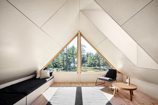 A small loft space sits above the living room and overlooks views of the forest and sea.