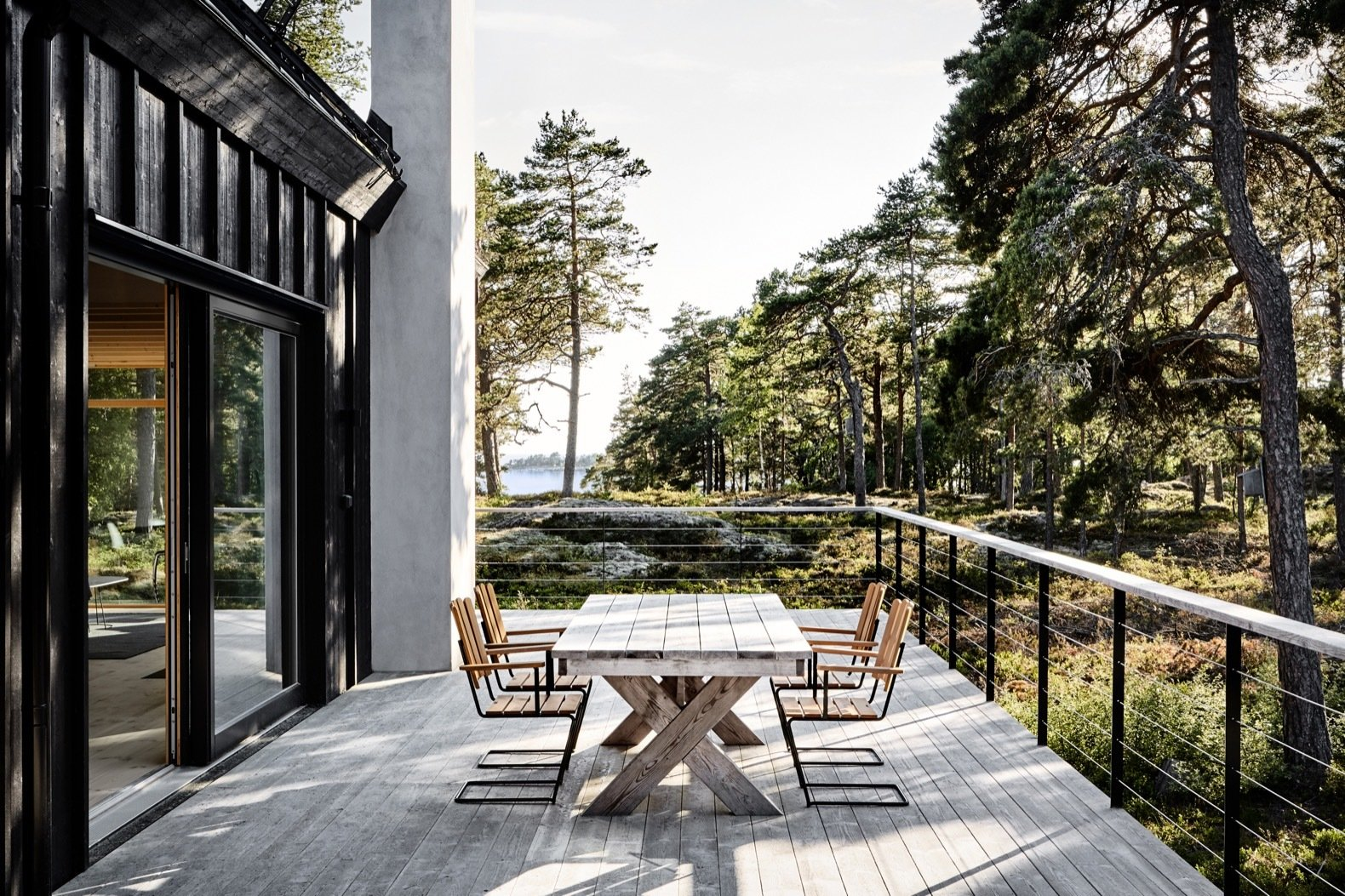 Outdoor, Shrubs, Grass, Wire, Large, Trees, Wood, Side Yard, Boulders, Woodland, and Horizontal The exterior decks are made of silicon-modified pine from OrganoWood.  Best Outdoor Wire Trees Photos from An Inspiring Island Retreat Mixes Scandinavian Style With Japanese Simplicity