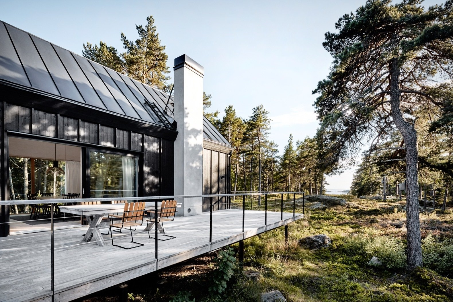 Outdoor, Wood Patio, Porch, Deck, Woodland, Large Patio, Porch, Deck, Horizontal Fences, Wall, Side Yard, Trees, Shrubs, Boulders, and Wire Fences, Wall Elevated on steel posts, the central volume and exterior deck project west toward the sea.    Photo 8 of 16 in An Inspiring Island Retreat Mixes Scandinavian Style With Japanese Simplicity