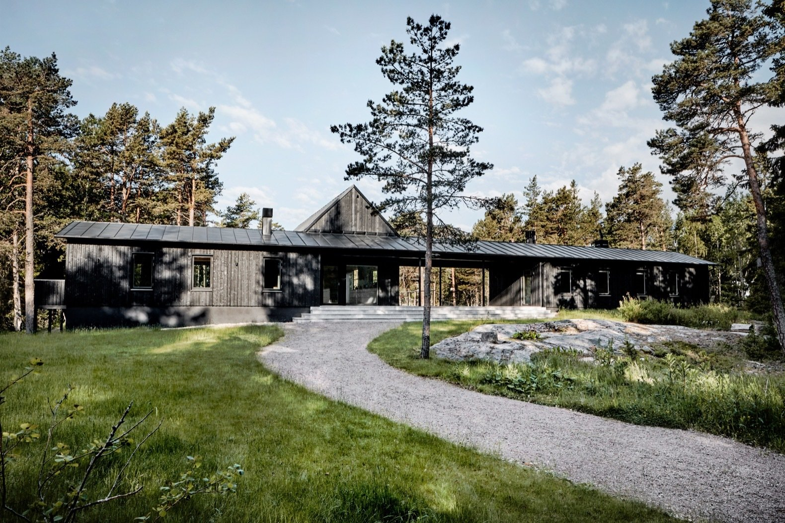 Outdoor, Hardscapes, Front Yard, Grass, Concrete Patio, Porch, Deck, Boulders, Walkways, Small Patio, Porch, Deck, Woodland, Shrubs, and Trees The home is accessed from the rear via a gravel path.  Photos from An Inspiring Island Retreat Mixes Scandinavian Style With Japanese Simplicity