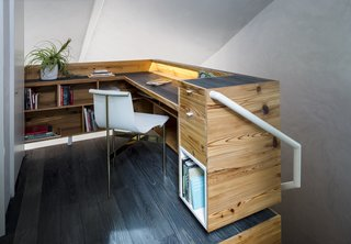 The office on the second floor backs up to the laundry unit concealed behind a door.