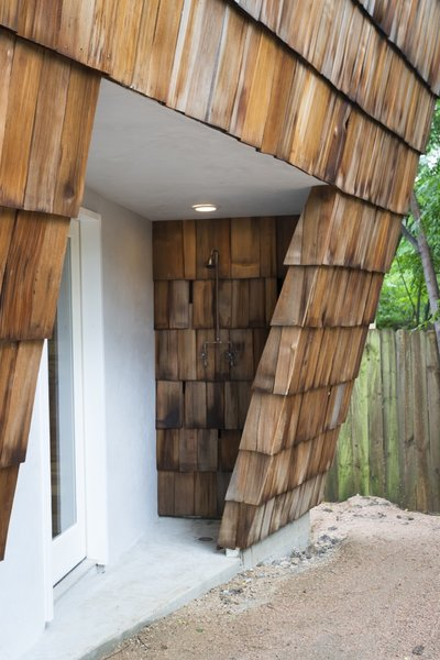 The angled walls have created opportunity for a sheltered porch and outdoor shower.