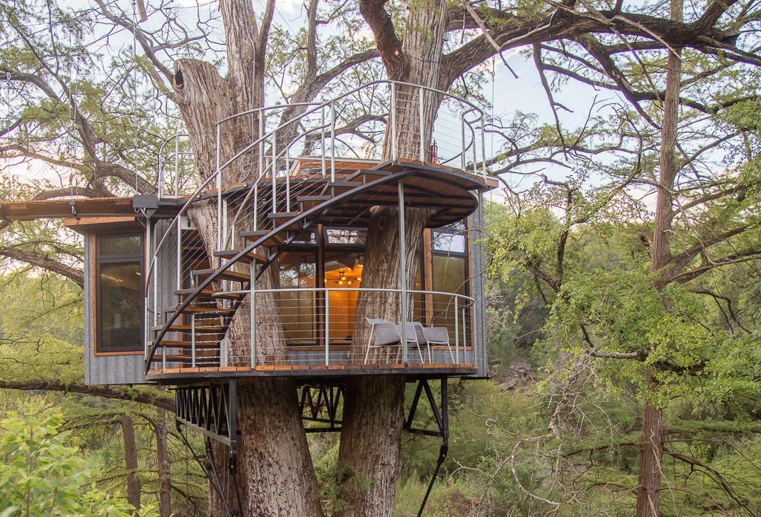 Exterior, Treehouse, Metal, Flat, and Metal ArtisTree's cabin towers 25 feet above the stream of water below, and it's anchored by ropes, chains, and cables.  Exterior Metal Treehouse Photos from Escape to the Texan Treetops in This Eco-Luxe Treehouse