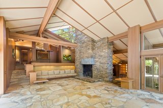 A monumental double-faced stone fireplace anchors the living room.