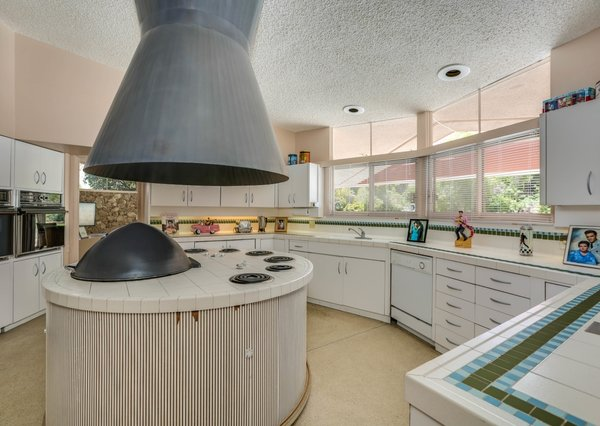 An oversized hood and a circular cooktop station is located in the round kitchen.