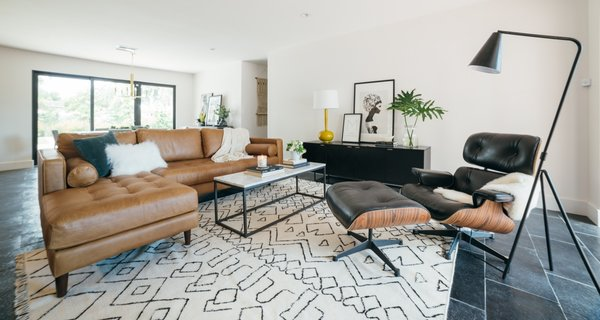 The newly renovated living room includes new, black limestone floors, a Sven Leather Couch by Article, and a West Elm coffee table. The rug is by Surya.