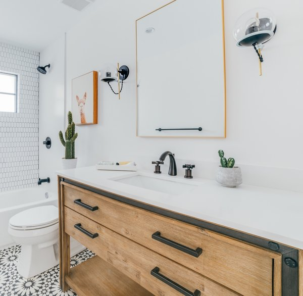 The new hall bathroom features Agdal Black cement floor tiles from Moroccan Mosaics, a vanity by Sage Hill Designs with a white quartz countertop by Stone Design by Santos, and a CB2 mirror.