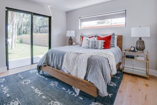 A look inside one of two guest bedrooms. The floors are wire-brushed, wide plank oak from ProSource. The bed and rug are from Four Hands while the side tables are from West Elm. The lamps are from Home Goods.