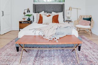 The bed is from Four Hands. The bench is from CB2, and the rug is Loren by Jaipur Rugs. To the left of the bed is a West Elm end table and wall-mounted sconce.