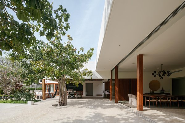 """""""A three-foot platform raises the main floor level from the ground, protecting the house against recurring floods,"""" explains the firm. """"This difference of level between the interior and exterior was used to create sloped gardens that work as thermal buffer zones."""""""