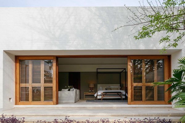 Massive, timber-framed sliding doors connect the master bedroom with the outdoors.
