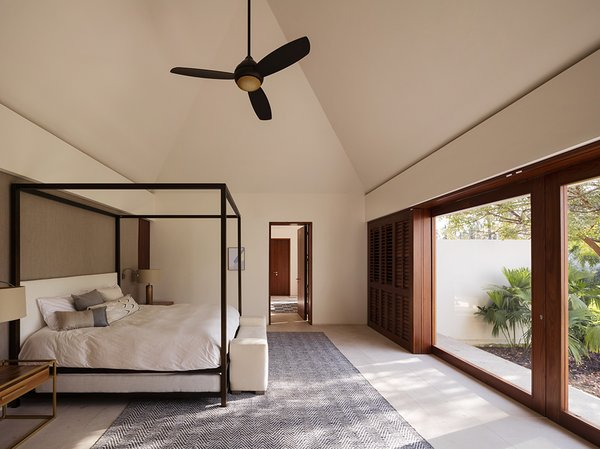 The master bedroom faces walls of glazing that frame tropical views. The bedroom connects to the master bath with a double vanity as well as a spacious walk-in closet in a separate room. The floors are Galala marble.
