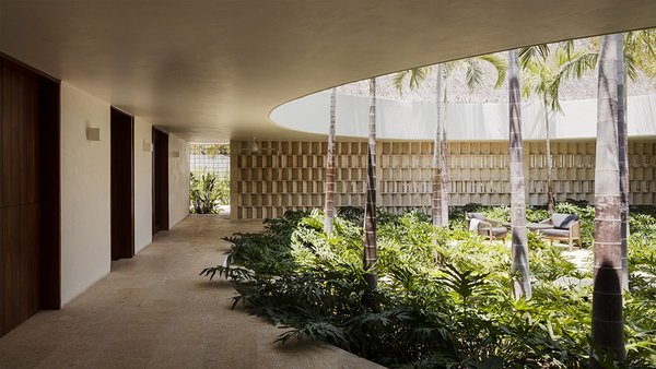 A limestone partition wall screens the indoor courtyard from the garage.