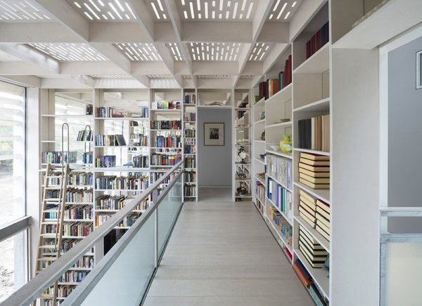 """""""A tall south-facing library, bounded by mirror-backed shelving and a light-modulating canopy, evokes a forest clearing in the heart of the house,"""" notes the firm."""