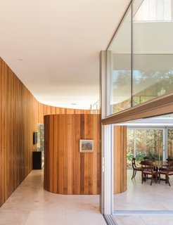 The kitchen pantry is housed in a curved, free-standing structure that's also wrapped in Western Red Cedar.