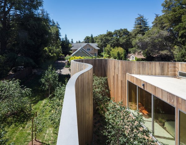 The massive curving wall serves as an alternative to the perimeter fence that's common to the neighborhood, an area which the architects says has developed a hodgepodge of architectural styles.