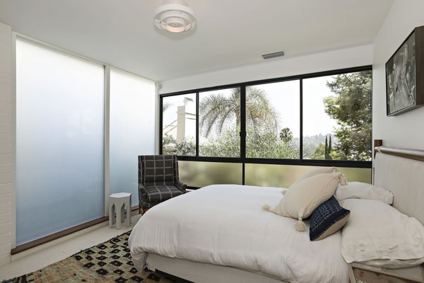 This guest room gets drenched in sunlight thanks to full-height frosted glass windows and operable glazing overlooking the city below.