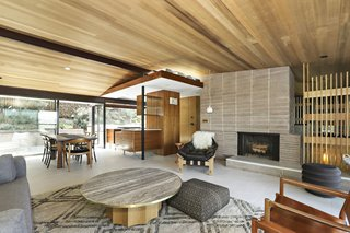 The original floor plan and design elements remain—from the concrete block fireplace to the restored sconces. The vaulted ceiling is made from western red cedar.