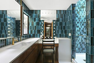 The master bath is covered in vibrantly colored tile.