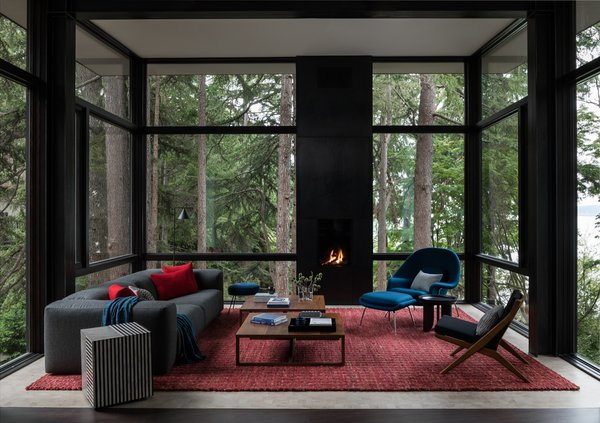 Enclosed in glass and elevated in the tree canopy, the living room is furnished with midcentury modern classics including a Case Kelston sofa from DWR and a Knoll Womb chair and ottoman. The custom red wool rug is from Driscoll Robbins.