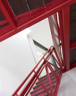Painted a vibrant red (Benjamin Moore Chili Pepper 2004-20), the stairs offer a playful splash of color against the white walls.