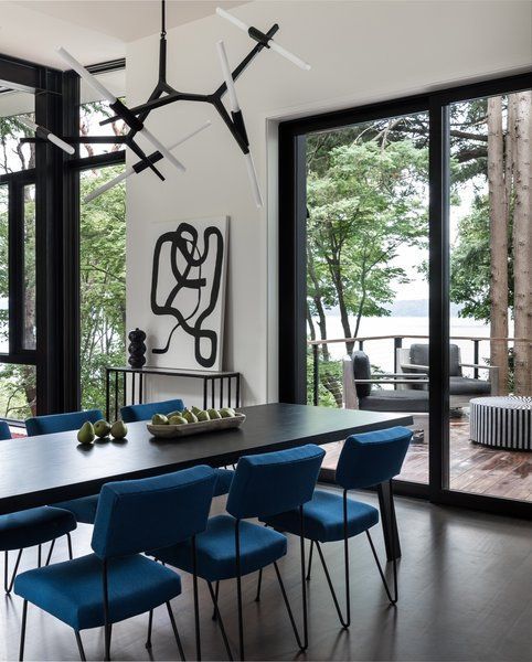 The dining room features a striking Agnes 10-light chandelier by Lindsey Adelman for Roll & Hill. Below, a Montis Doble table is combined with vintage Case Study iron chairs upholstered in blue fabric. The artwork, titled Linger, is by Kate Neckel via Winston Wächter.
